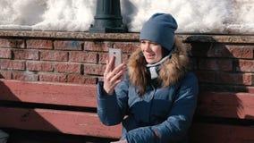 妇女在坐在冬天公园的手机的录影闲谈谈话 影视素材
