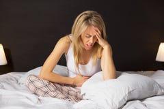 妇女在坐在床上的痛苦中 图库摄影