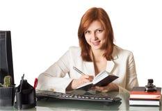 妇女在坐在服务台的笔记本写 免版税库存图片