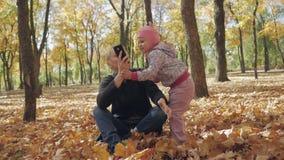 妇女在坐在秋天公园的电话谈话,并且一个小女儿附近使用 股票录像