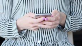 妇女在城市递发短信在智能手机 股票录像