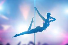 妇女在夜总会执行性感的杆舞蹈 免版税库存照片