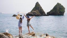 妇女在大石头站立在礁石的背景的海 股票视频