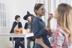 妇女在女孩` s面孔绘一只小猫的构成一个党的在Haloween 库存图片