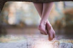 妇女在她的在一本日志的腿垂悬在湖上 免版税库存图片