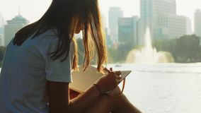 妇女在她的坐在城市公园的笔记薄书写在有喷泉的池塘附近 影视素材