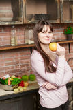 妇女在她的手上拿着一个桔子 在家烹调在厨房里的少妇 健康的食物 饮食 免版税库存图片