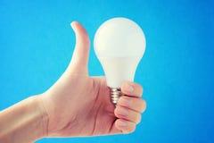 妇女在她的手上拿着一个电灯泡并且显示l 免版税图库摄影