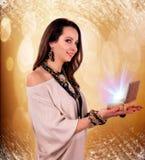 妇女在她的手上拿着光在抽象背景的一个箱子 库存照片