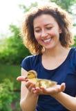 妇女在她的手上的拿着小的黄色鸭子 免版税库存照片
