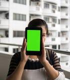 妇女在她的手上的拿着片剂有空白的绿色屏幕的 库存照片