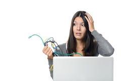 妇女在她的手上的拿着缆绳,当使用膝上型计算机时 库存图片