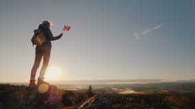 妇女在她的手上站立在山顶部,拿着挪威的旗子 盼望前面史诗风景 免版税库存图片