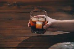 妇女在她的手可乐举行用科涅克白兰地或rom在玻璃和冰块在木背景 库存图片