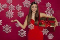 妇女在她的手,它上的拿着一件礼物下雪在她的其他ha的` s 免版税图库摄影