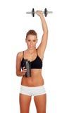 妇女在她的训练以后,饮用的蛋白质震动和有app的 免版税图库摄影