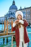 妇女在威尼斯,意大利在显示心形的手的冬天 图库摄影