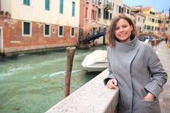 妇女在威尼斯,意大利 摆在威尼斯式运河背景的女孩 可爱的妇女在威尼斯湾 免版税库存图片