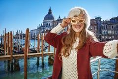 妇女在威尼斯,采取selfie的意大利,当在威尼斯式面具时 库存照片