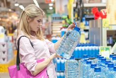妇女在存储采购一个瓶水 免版税库存图片