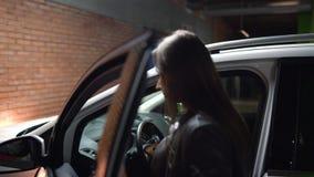妇女在它去她的汽车,打开门并且坐下 影视素材