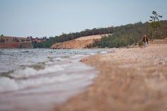 妇女在安静的海滩走 免版税库存图片