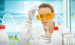 妇女在实验室用设备,吸移管 免版税图库摄影