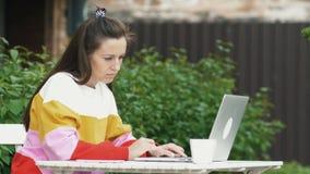 妇女在室外咖啡馆的用途膝上型计算机 股票录像