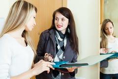 妇女在家回答在门的问题 免版税库存图片