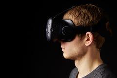 妇女在家坐佩带虚拟现实耳机的沙发 免版税库存图片