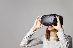 妇女在家坐佩带虚拟现实耳机的沙发 图库摄影