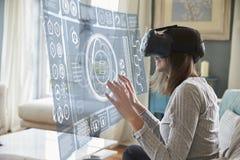 妇女在家坐佩带虚拟现实耳机的沙发 库存图片