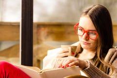 妇女在家坐椅子阅读书 免版税库存照片