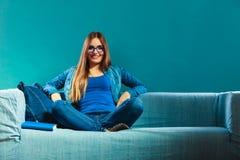 妇女在家坐长沙发阅读书 免版税库存图片
