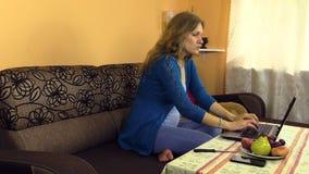 妇女在家工作怀孕到膝上型计算机,在桌上的果子电话 股票录像