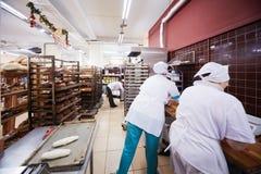 妇女在家庭食物超级市场面包店工作  免版税库存图片