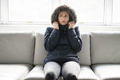 妇女在家得在沙发的寒冷有冬天外套的 图库摄影