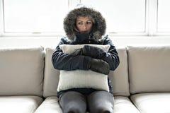 妇女在家有在沙发的流感有冬天外套和枕头的 免版税库存图片