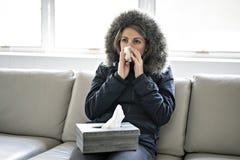 妇女在家有在沙发的流感有冬天外套的 库存照片