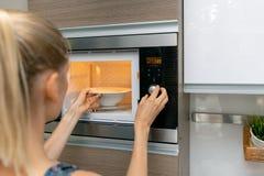 妇女在家给在微波炉的食物加热 免版税库存照片