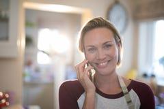 妇女在家谈话在手机在厨房里 免版税库存图片