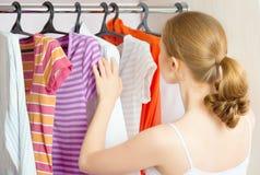 妇女在家选择在衣橱壁橱的衣裳 免版税库存图片