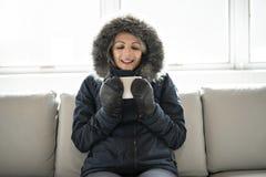 妇女在家食用在沙发的冷的饮料咖啡有冬天外套的 免版税图库摄影