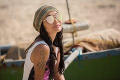 妇女在小船佩带的太阳镜和帽子附近坐 免版税库存照片