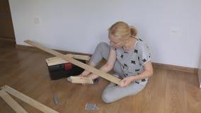 妇女在屋子里坐地板打开在商店买的一个木机架 家具装配  影视素材