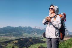 妇女在山上面的背包徒步旅行者旅客  免版税库存照片