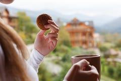 妇女在山区度假村在她的手上拿着咖啡和燕麦曲奇饼 有茶杯子和快餐的女性与森林和 免版税库存照片