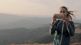 妇女在山土坎的徒步旅行者身分在日落和拍照片 股票视频