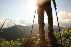 妇女在山峰岩石的远足者立场 图库摄影