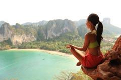 妇女在山峰峭壁的实践瑜伽 库存图片